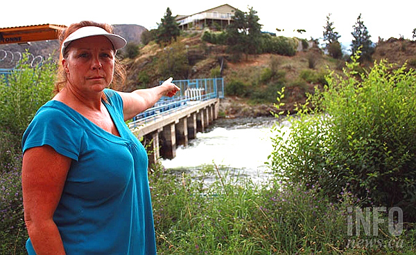 Okanagan Falls resident Melody Walker points to the east bank of the Okanagan River to her family's property (STEVE ARSTAD -- InfoTel Multimedia)
